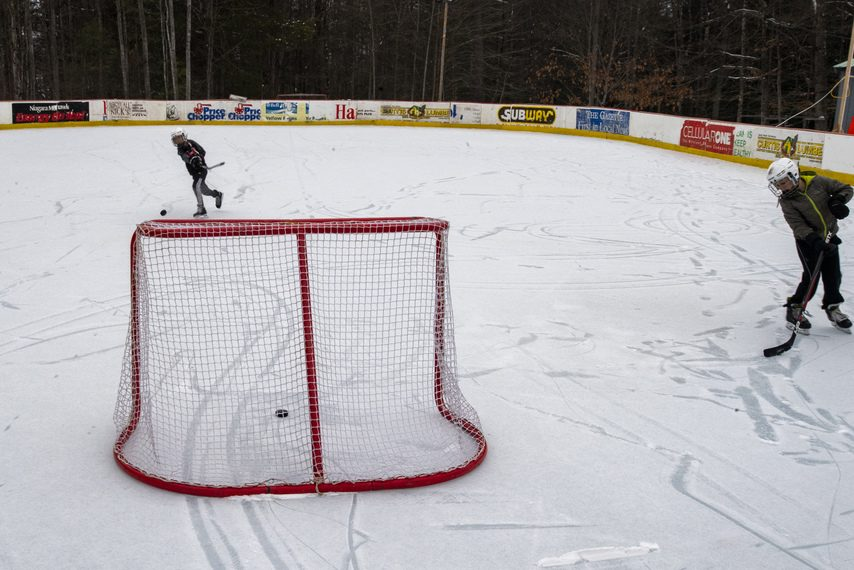 Zeke Klueg, 12, of Northville takes a shot on net with his brother Torrin, 9, while playing hockey on the family's backyard ice rink on Wednesday.