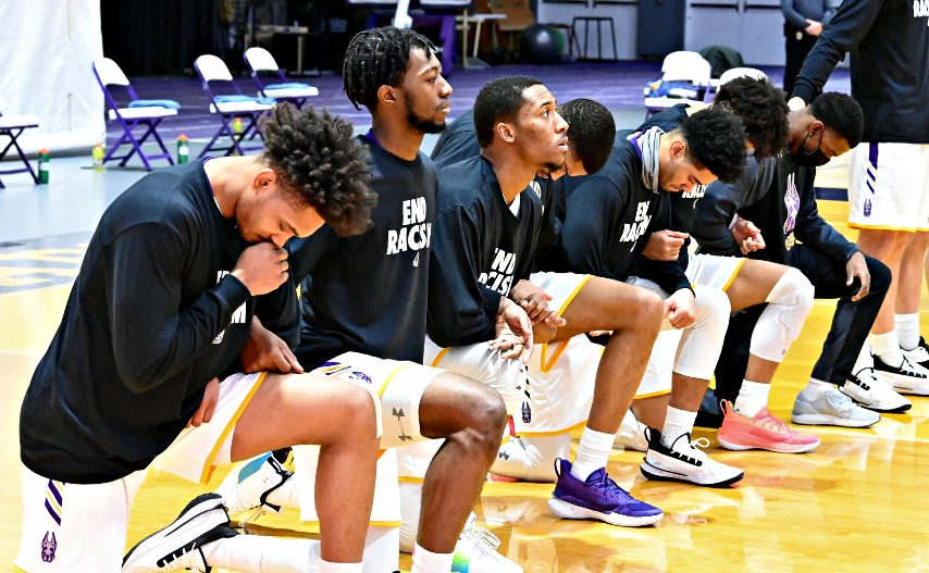 Seven UAlbany men's basketball players take a knee before Saturday's game in Albany. (Bob Mayberger/UAlbany Athletics)