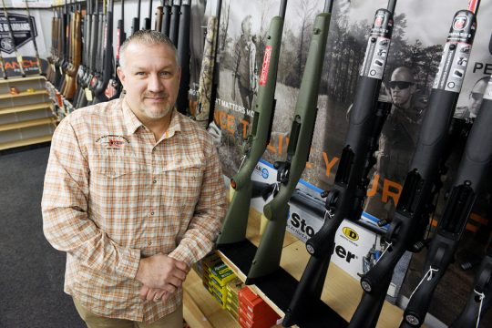Frank's Gun Shop owner John Havlick stands in front of a row of shotguns in his store on Route 30 on Monday.