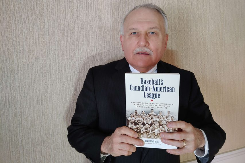 "Author Dave Pietrusza of Glenville holds his book ""Baseball's Canadian-American League,"" in which he documents some of the exploits of Tommy LaSorda as a pitcher for the Schenectady Blue Jays."