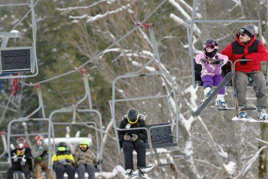 Dan Zielinski, of Fort Johnson, rides the ski lift on the bunny mountain with his daughter Vada, 5, Monday