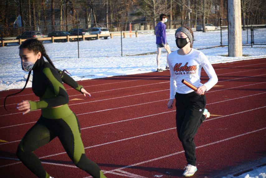 Mohonasen junior Zionna Perez-Tucker reaches back for the baton to start the second leg of the 4x200-relay Monday afternoon as the Mighty Warriors took their indoor scrimmage with Schalmont outside. (Stan Hudy/The Daily Gazette)