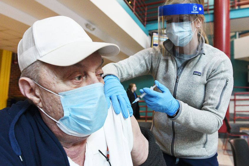 ERICA MILLER/THE DAILY GAZETTE Bill Smith of Rotterdam gets a shot of the Moderna COVID-19 vaccine Monday from pharmacist Beth Hirming at SUNY Schenectady County Community College.