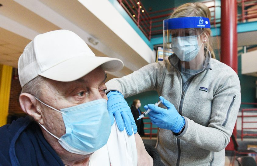Bill Smith, 75-years-old of Rotterdam, receives his Moderna COVID-19 vaccine from volunteer and pharmacist with Esperion Therapeutics Beth Hirming Monday