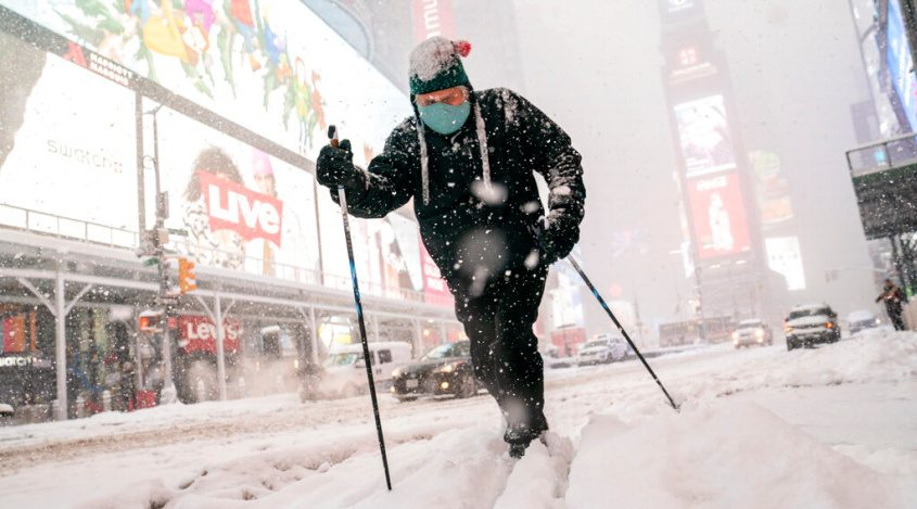 Steve Kent skis through Times Square during a snowstorm Monday. (AP Photo/John Minchillo)