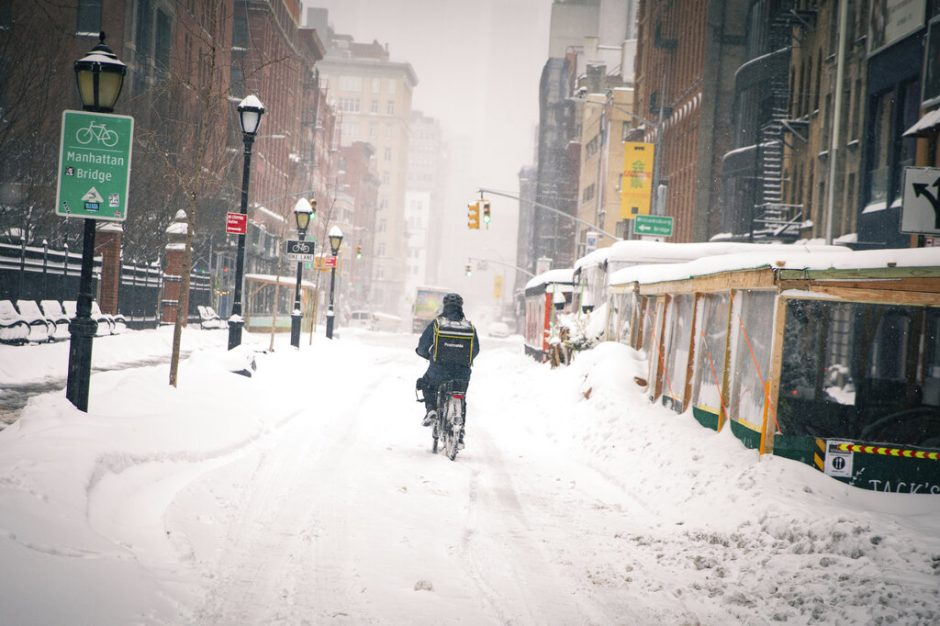 A bicycle food delivery worker rides his bike through Manhattan's Soho neighborhood, Monday, in New York