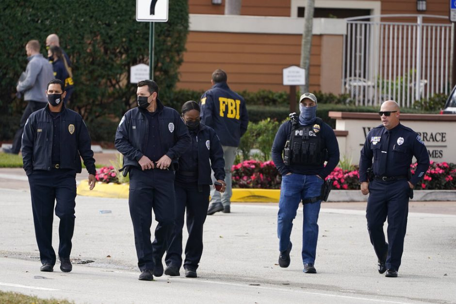 Law enforcement officers walk near the entrance to an apartment complex where a shooting wounded several FBI agents while serving an arrest warrant Tuesday in Sunrise, Fla.