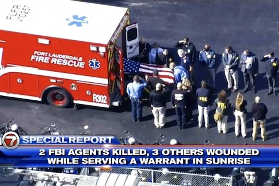 Law enforcement officials from numerous agencies line up to pay their respects as a flag-covered body was removed from the vehicle and taken inside. (WSVN-TV via AP)