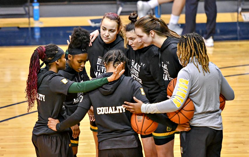 The Siena women's basketball team huddles prior to the start of Wednesday's game at Monmouth. Only seven Saints were able to travel for the game because of issues related to the pandemic, and only six were available to play. (Photo courtesy Monmouth Athletics)