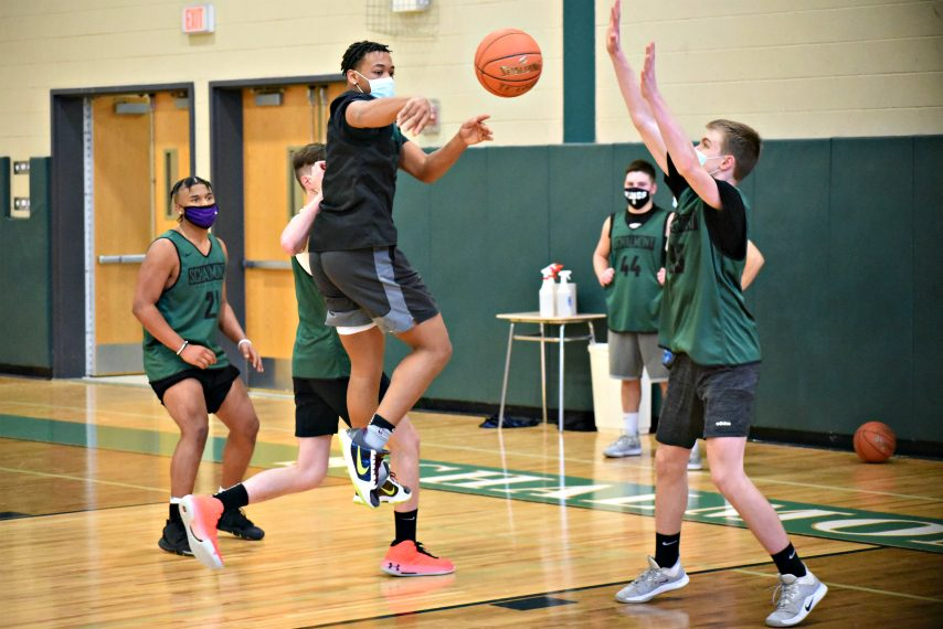 Rodney Parker dishesthe ball in front of teammate Paul Brosious during Monday's practice at Schalmont High School. The Sabres host LaSalle Friday in their season opener.(Stan Hudy/The Daily Gazette)