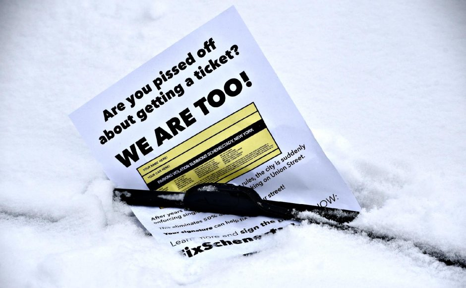 A flier on Tuesday is uncovered on the windshield of a vehicle parked on Front Street in Schenectady in the Stockadeneighborhood regarding recent parking tickets in the area after a snowfall.