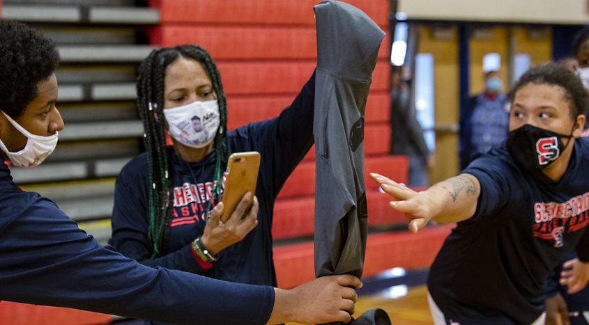 Schenectady basketball players touch Naylon Carrington's warm up jersey held by his mother Sondra Banks before the game Saturday