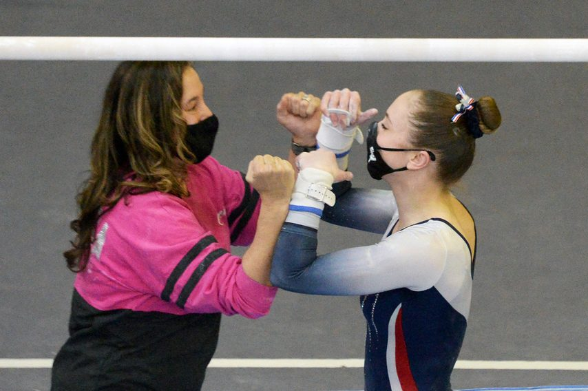 Ava Dallas of the Saratoga Springs High School gymnastics team receives congratulations from her coach, Deb Smarro, after performing on the uneven bars at the Suburban Council championship meet at World Class Gymnastics Academy in Latham Sunday. (Erica Miller/The Daily Gazette)