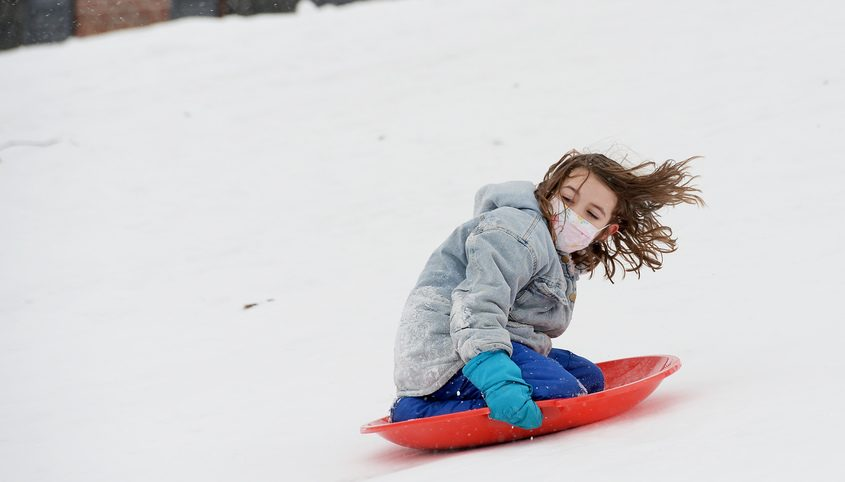 Tullia Epstein, 6 of Schenectady, smiles while sledding down a hill during their winter break from school at Schenectady Municipal Golf Course in Schenectady Monday