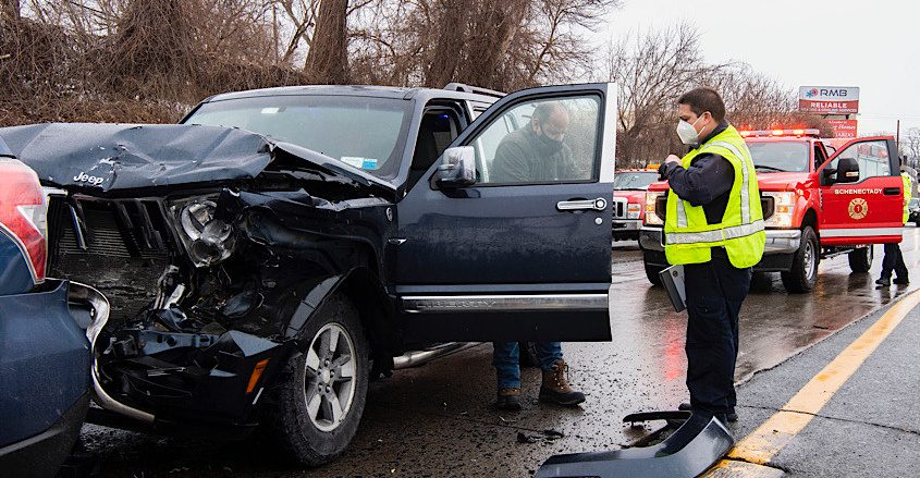 Schenectady firefighter Lt. Darwen Van Natten checks the condition of a driver Tuesday after a crash on the Crosstown