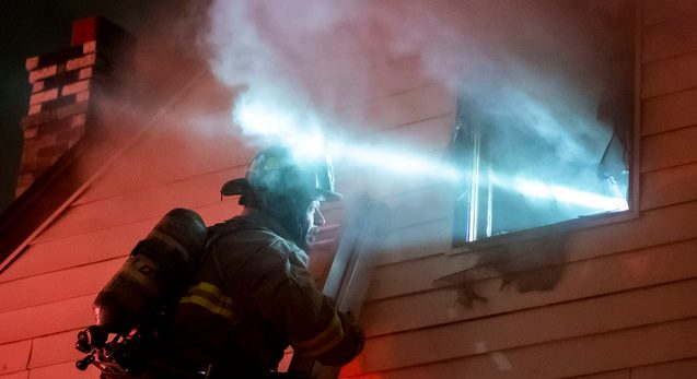Schenectady firefighter Michael Mareno talks to firefighters from the top of a ladder while fighting a house fire at 1629 Chrisler Avenue Tuesday evening.