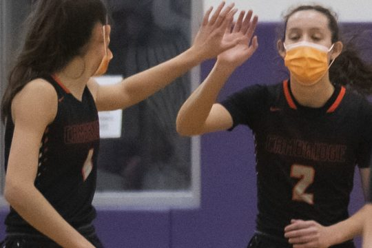 Lilly Phillips of Cambridge high fives her twin sister Sophie Phillips during a game against Duanesburg on Tuesday.