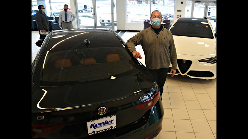 General Manager Frank Salamida stands between two Alfa Romeo Giulia sport utility vehicles at Keeler Motor Car Company in Latham on Tuesday.