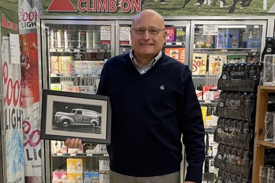 """President John """"Jack"""" Minogue Jr. standing in the Saratoga Springs store on West Avenue holding a photo of his grandfather's M.T. Minogue beer truck"""