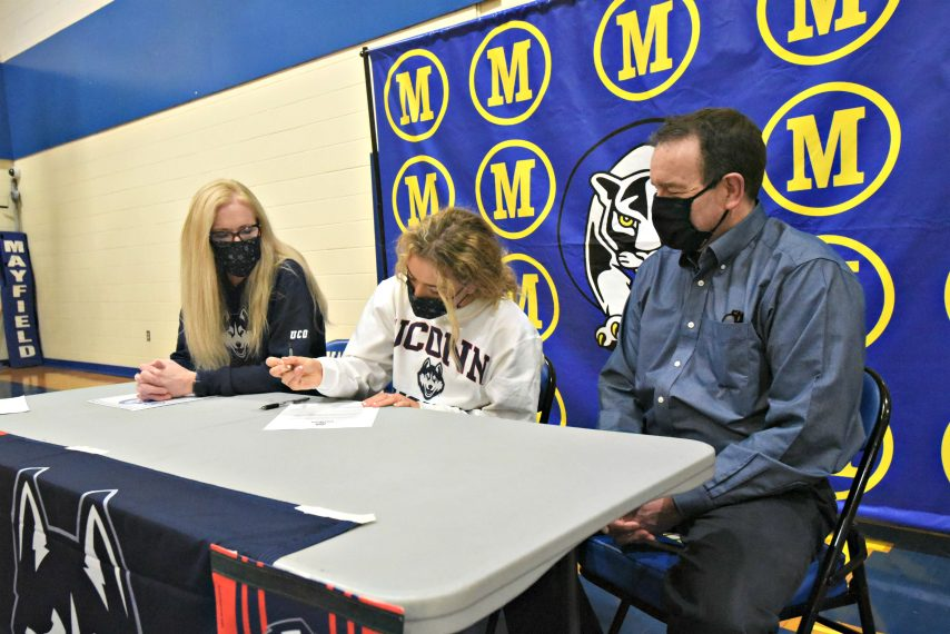 Mayfield's Madison Relyea, center, signs her National Letter of Intent to compete at UConn as her mother, Kara, and father, Chris, watch Thursday.