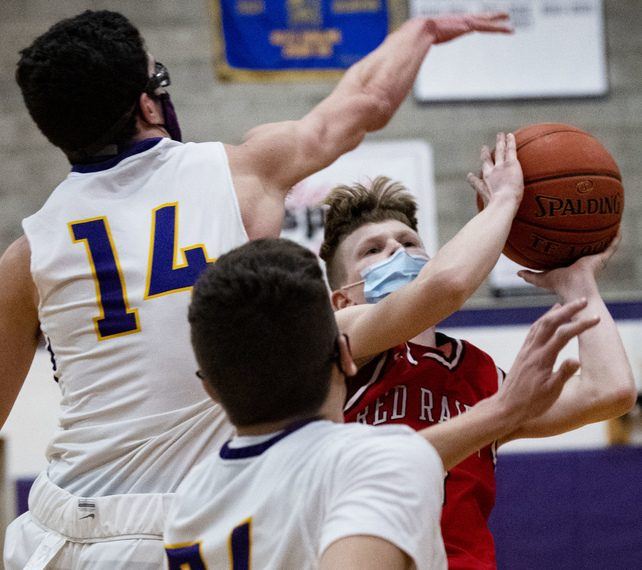 Kyle Johnson of Mechanicville takes a shot between Hayden Day and Aidan Lambert of Saratoga Central Catholic in a boys' basketball game Friday night.