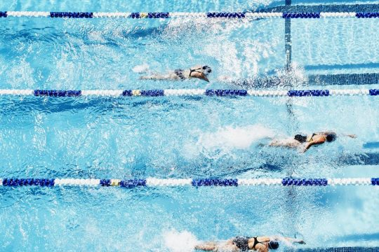 competitive-swimmers-racing-in-outdoor-pool-royalty-free-image-1584113727.jpg