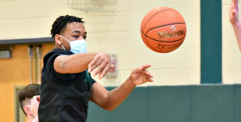 Rodney Parker dishes a pass in front of teammate practice at Schalmont High School last month