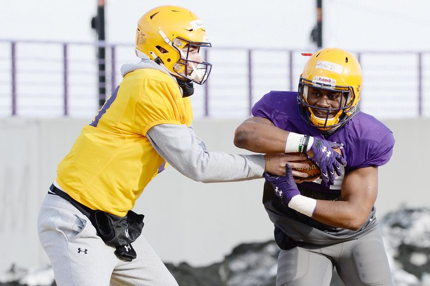 UAlbany quarterback Jeff Undercuffler (left) hands off to running back Karl Mofor during a Feb. 24 practice at Tom & Mary Casey Stadium.