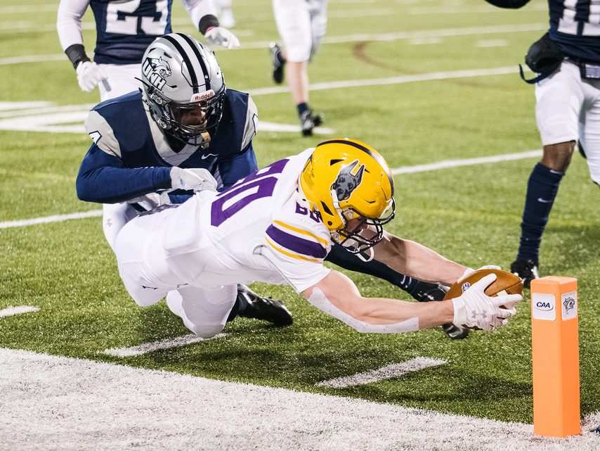 UAlbany wide receiver Mike Gray dives for the pylon to score a touchdown against New Hampshire during a CAA football game on Friday in Durham, New Hampshire.