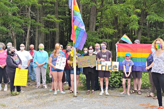 Members of the community stand at the New York state flag pole where a new Pride flag was raised the morning of June 9, 2020, at the Woods Hollow Preserve in Milton. It replaces two Pride flags that were previously stolen.