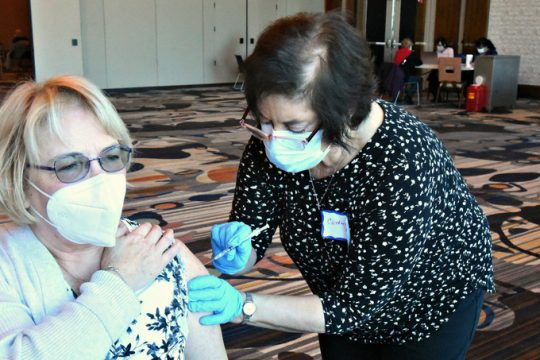 Catherine Lucas, RN of Niskayuna injects Eileen Buono of Schenectady Sunday morning at Rivers Casino, part of a mass vaccination event where more than 1,100 doses of the Pfizer vaccine were distributed to Schenectady County residents.