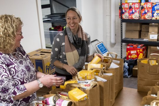 Erica Reichelt, left, treasurer of Nisky NOW, and President Jessica Brennan sort through bags of groceries in the basement of Van Antwerp Middle School Wednesday.