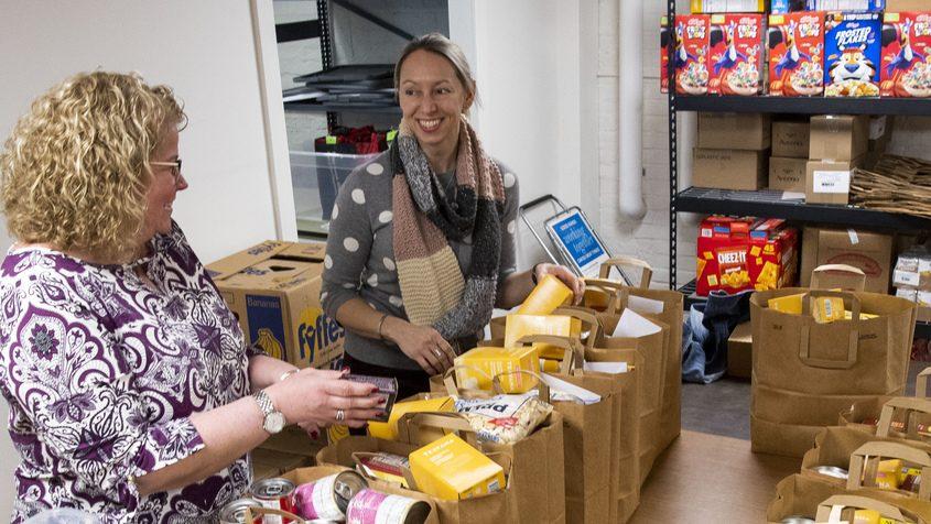 Erica Reichelt, left, treasurer of Nisky NOW, and President Jessica Brennan sort through bags of groceries in the basement of Van AntwerpMiddle School Wednesday.