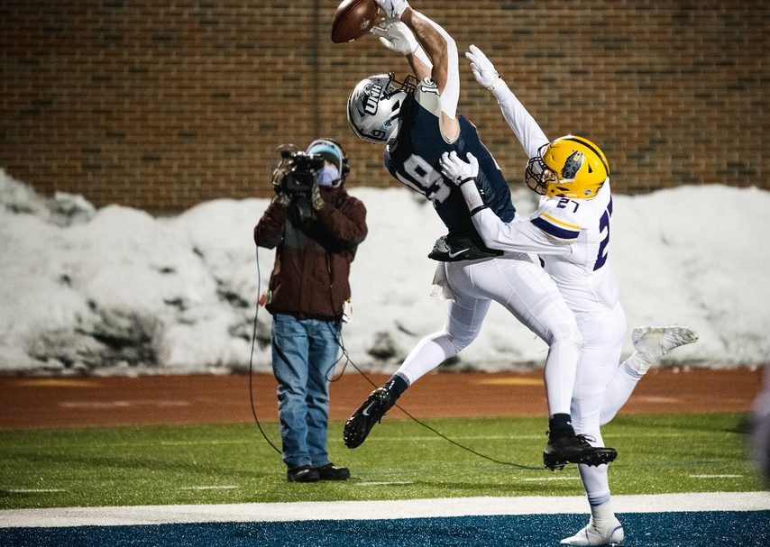 UAlbany safety Hayden Specht (right) breaks up a pass in the end zone intended for New Hampshire receiver Nick Lorden during a CAA football game last Friday in Durham, New Hampshire. (Photo courtesy China Wong/UNH Athletics)