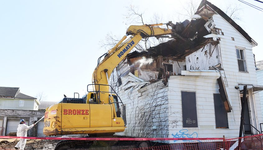 Bronze Contracting demolishes an old house at 1052 Barrett St. in Schenectady on Friday.