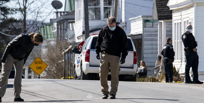 State police detectives search James Street in Amsterdam for evidence Friday.