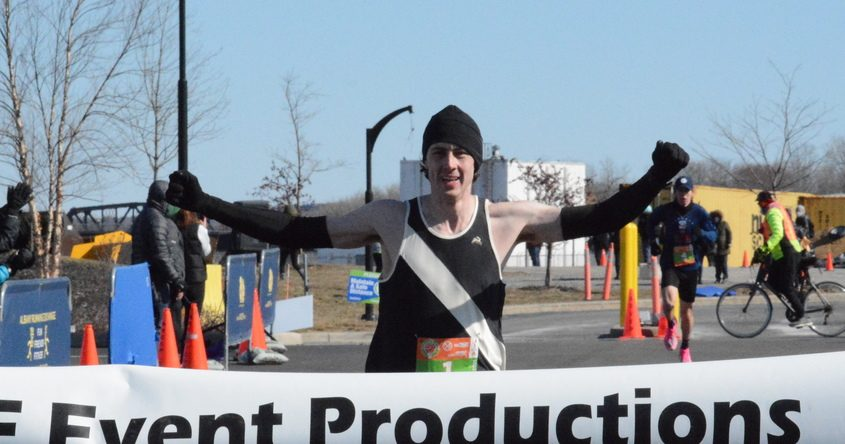 Brian Reis raises his arms in triumph as the first runner to cross the finish line Saturday