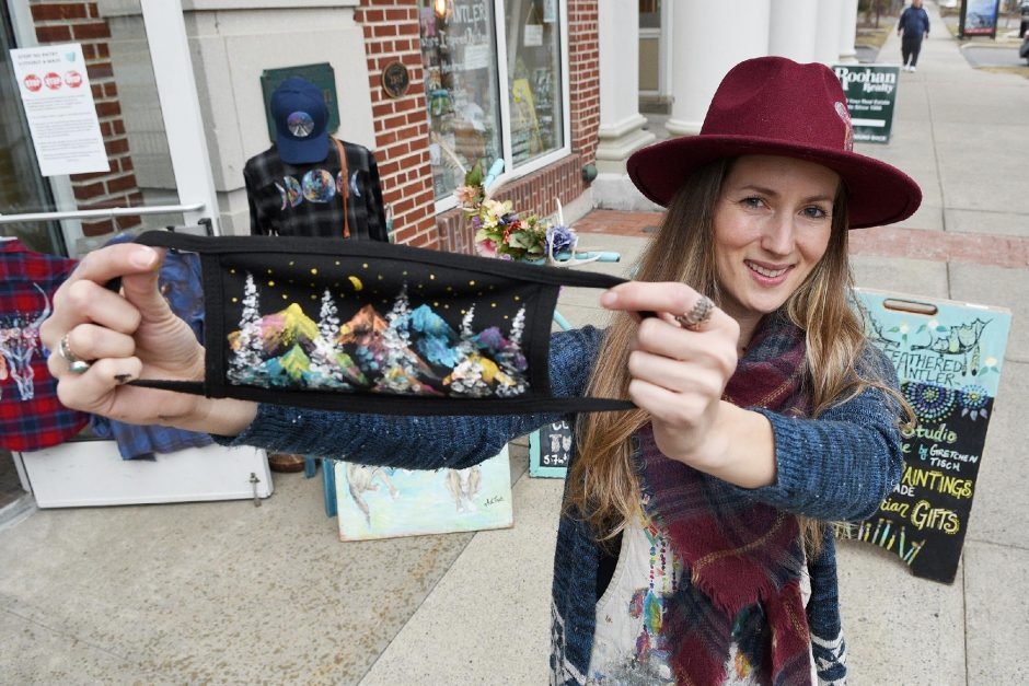 Feathered Antler owner Gretchen Louise Tisch holds one of her handprinted masks outside her store on Broadway in Saratoga Springs on March 11.