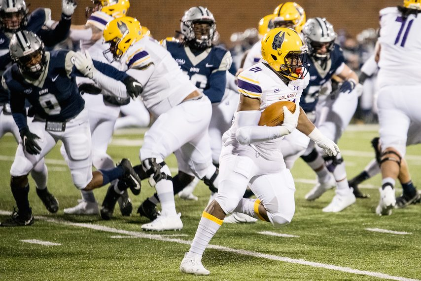 UAlbany running back Karl Mofor carries the ball against New Hampshire during a CAA football game on Friday, March 5 in Durham, New Hampshire. (Photo courtesy China Wong/UNH Athletics)