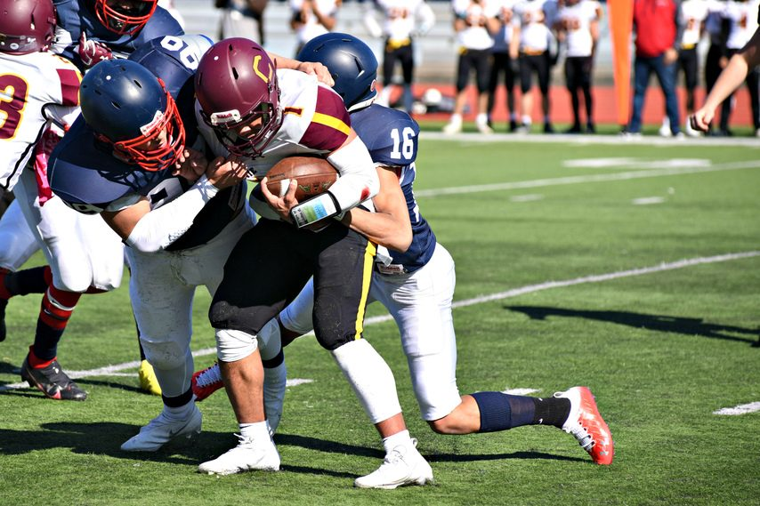"""Schenectady's Joel """"J.J."""" Reyes (99) and Jakeim Edge (16) wrap up Colonie quarterback Donald Francis Saturday afternoon against Colonie in Class AA football action at Schenectady High School."""