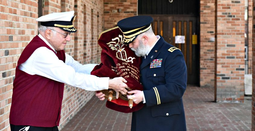 Chaplin Major Moshe Lans - U.S. Army embraces a Torah handed to him by Dr. James Strosberg, past president of Congregation Beth Israel after a ceremony Sunday