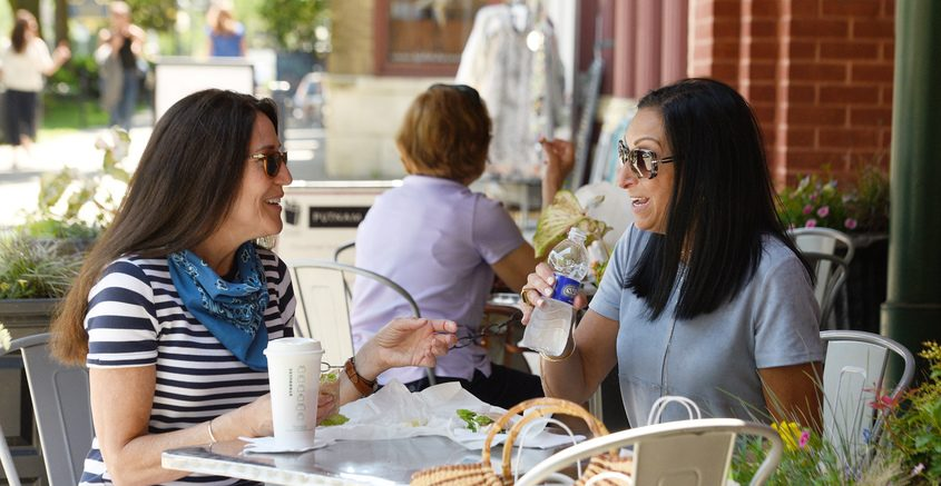 Janine Robinson, left, and Lynn McColl, both of Saratoga Springs, enjoy lunch at Putnam Market on Broadway in Saratoga Springs on June 4. Tourism officials expect business to pick up this year.