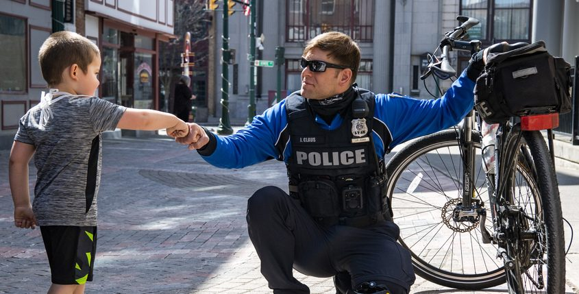 Schenectady police officer James Claus fist-bumps 4-year-old Shawn Fennicks on the Jay Street Pedestrian Mall Tuesday. Shawn stopped to talk to officer Claus about his bicycle and what he carries on it.