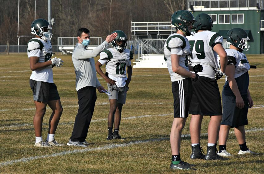 Schalmont coach Joe Whipple stands between running back Rodney Parker, left, and quarterback Trent Randle while talking to his offensive unit during Tuesday's practice at the Schalmont High School.