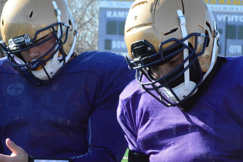 Amsterdam offensive linemen Alex Simon (left) and Christian Robinson listen to a playcall in the huddle during football practice on Monday, March 15 at Lynch Literacy Academy.