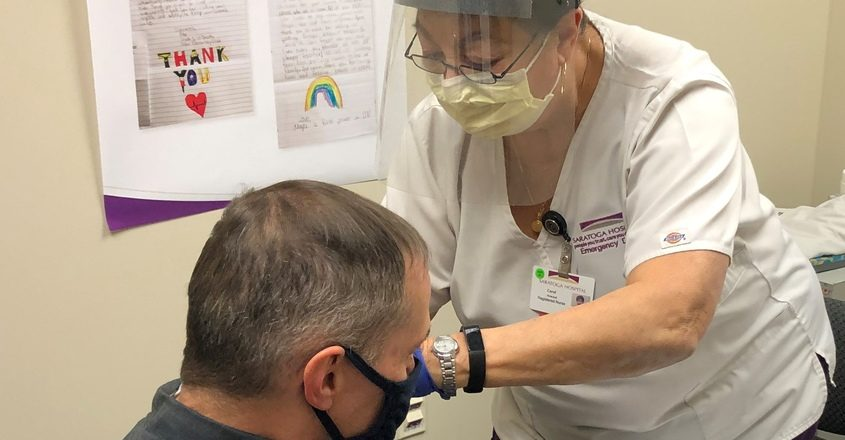 Registered nurse Carol Howard delivers a dose of COVID vaccine at Saratoga Hospital on Dec. 22, the day the hospital set up its in-house vaccination clinic.
