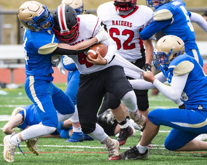Mechanicville's Cameron Napier is wrapped up by Granville's Matthew Barlow, left, and Skylar Schinski during Saturday's Class C football game at Mechanicville High School.