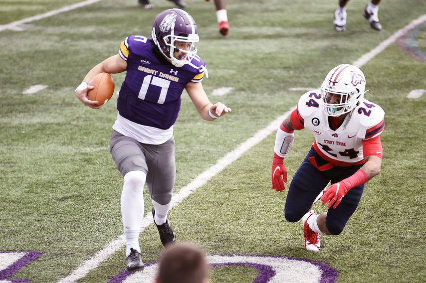 UAlbany quarterback Braeden Zenelovic carries the ball while pursued by Stony Brook's Nick Chimienti (24) on Saturday, March 27 at Tom & Mary Casey Stadium in Albany. (Photo courtesy Kathleen Helman/UAlbany Athletics)