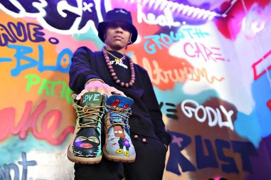 Raè Frasier, creator of the Art Mon3y brand, shows off a pair of custom Timberland boots in front of her Realm of Positivity mural in her home studio in Schenectady.