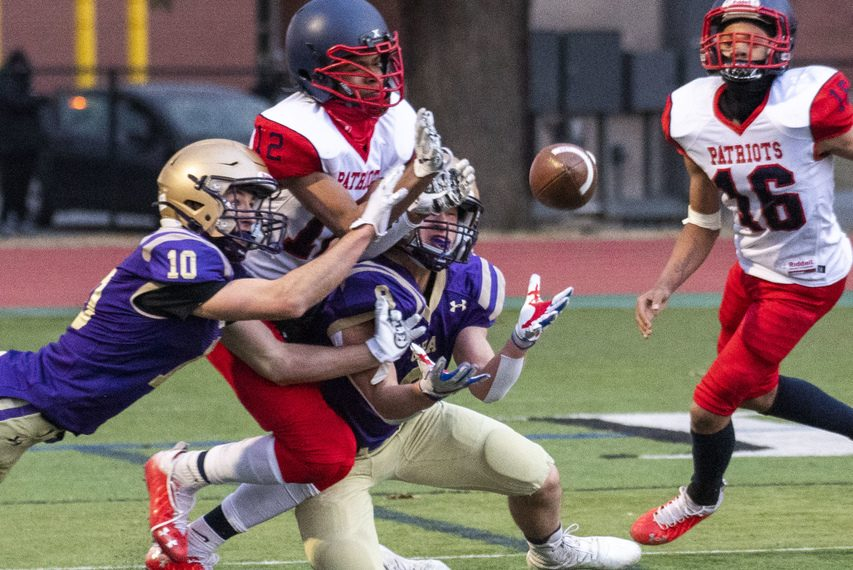 Schenectady's Denzere Woolcock(12) breaks up a pass intended for Christian Brothers Academy's Jacob Iacobaccio while beinghit by CBA's Dylan Jones (10) with Schenectady teammate Jakiem Edge (16) at right on Friday.